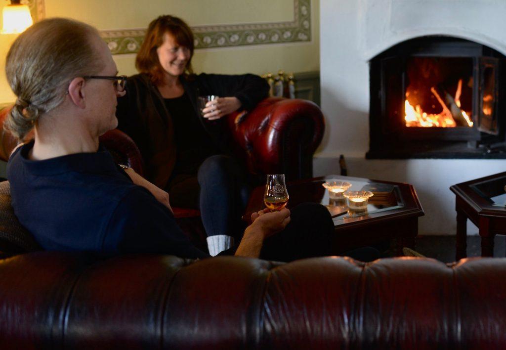 Gäster som myser med whisky framför brasan